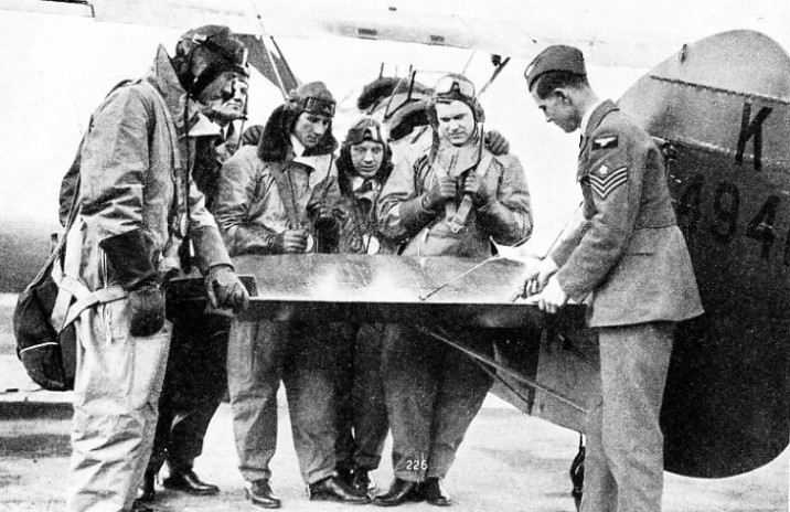 SHORT-SERVICE PILOTS studying the construction of the elevators of an aeroplane