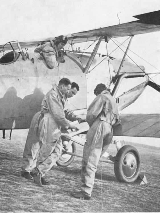 VOLUNTEER RESERVE PILOTS DISCUSSING DETAILS OF A FLIGHT before taking off in a Hawker Hart Trainer