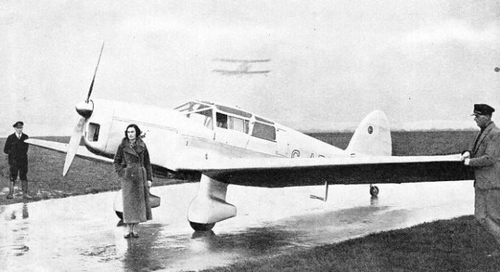 Miss Jean Batten is standing beside her Percival Gull aircraft in which she won the Britannia trophy for 1935